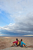 Couple sitting together in badlands section of Anza Borrego State Park and admiring landscape, California, USA