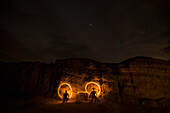 Night time image of a couple light painting and making designs with flashlights in Anza Borrego Desert State Park, California.