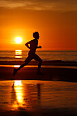 Silhouette of runner at sunset on La Jolla Shores Beach, San Diego, California, USA
