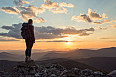 A young woman views the sunset from Mount Abraham, near the Appalachian Trail in Maine's western mountains.