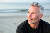 Portrait of gray-haired man sitting alone on coastal beach and looking away, Dennis, Massachusetts, USA