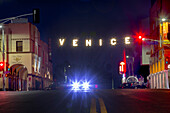 Famous Venice Beach sign lit up at night, Los Angeles, California, USA