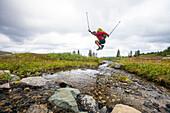 Side view of man jumping across small stream, Merritt, British Columbia, Canada