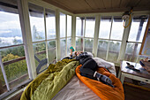 Woman relaxing with phone on bed inside Pickett Butte Fire Lookout near Tiller Oregon, USA