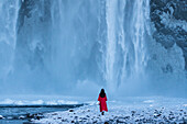 women in a red winter coat in front of the impressive Skogafoss waterfall, southcoast, Iceland