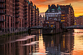 Wasserschloss building at the historical warehouse complex (Speicherstadt) seen from Poggenmuehlenbrucke during sunset, Hamburg, Germany, Europe