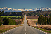 Open road on State Highway 6 near Cromwell, Central Otago with views to the ski fields at Wanaka, Otago, South Island, New Zealand, Pacific