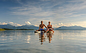A young couple on their SUP boards on the Chiemsee, in the background the Chiemgau Alps, Chieming, Upper Bavaria, Germany
