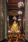Wat Bowonniwet Vihara, monks at evening praying,Bangkok, Thailand