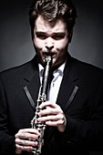 Portrait of Young Male Musician Playing Clarinet.