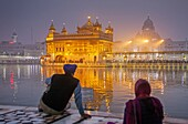 Pilgrims and sacred pool Amrit Sarovar, Golden temple, Amritsar, Punjab, India.