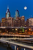Philly Skyline Full Moon - A view to the Philadelphia Skyline during the blue hour at twilight. The illuminated urban skyline shows One and Two Liberty Place along with the full moon rising.