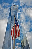 American Flag At World Trade Center WTC - The United States of America Flag sways in the wind with the Freedom Tower in the background.Blue skies and puffy clouds are reflected in the facade of One World Trade Center.