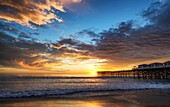 Vibrant, cloudy sunset view from Mission Beach with the Crystal Pier. San Diego, California.