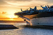 The USS Midway Museum Ship at San Diego Harbor against the background of the setting Sun. San Diego, California, USA.