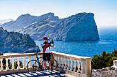 Cyclist takes souvenir photo, Cap Formentor, Tramuntana Mountains, Mallorca, Spain