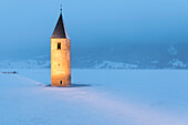 The submerged bell tower of Curon Venosta, province of Bolzano, Alto Adige district, Italy, under a snowfall