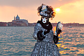 Typical mask of Carnival of Venice at San Giorgio island with Redeemer Church on background, Venice, Veneto, Italy