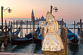A typical mask of Carnival of Venice in Riva degli Schiavoni with San Giorgio Maggiore Island on background, Venice, Veneto, Italy
