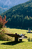 Girl relaxing on a bench in the Italian Dolomites Alps, Funes Valley, Trentino Alto Adige, Italy