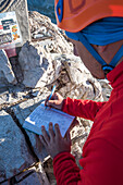 Sesto / Sexten, province of Bolzano, Dolomites, South Tyrol, Italy. Mountaineer sign the summitbook of Mount Paterno