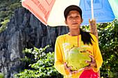 A woman selling coconut milk, El Nido, Palawan, Philippines, Asia