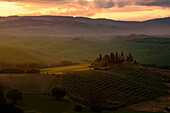Podere Belvedere, San Quirico d'Orcia, Siena province, Tuscany, Italy. Sunrise over the farmhouse and the hills.