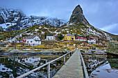 Wooden bridge leading towards Norwegian houses and mountains, Matterhorn of Lofoten, Reine, Lofoten, Nordland, Norway