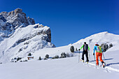 Two persons backcountry skiing ascending to Medalges, Geisler range in background, Medalges, Natural Park Puez-Geisler, UNESCO world heritage site Dolomites, Dolomites, South Tyrol, Italy