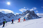 Several persons backcountry skiing ascending to Medalges, Geisler range in background, Medalges, Natural Park Puez-Geisler, UNESCO world heritage site Dolomites, Dolomites, South Tyrol, Italy