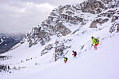 Three persons backcountry skiing descending from Forcella Roa, Forcella Roa, Natural Park Puez-Geisler, UNESCO world heritage site Dolomites, Dolomites, South Tyrol, Italy