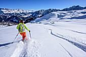 Woman backcountry skiing descending from Peitlerkofel, Peitlerkofel, Natural Park Puez-Geisler, UNESCO world heritage site Dolomites, Dolomites, South Tyrol, Italy