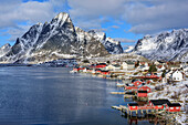 Snow-covered mountains with fisherman´s cabins and harbour of Reine, Reine, Lofoten, Nordland, Norway