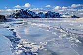 Vereister Strand mit verschneiten Bergen, Lofoten, Nordland, Norwegen