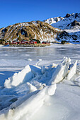 Sheet of ice in fjord with fisherman´s cabins in background, Lofoten, Nordland, Norway