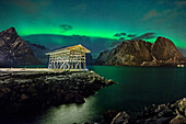 Illuminated shed for drying fish with polar lights and stary sky, northern lights, aurora borealis, Lofoten, Nordland, Norway