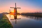 Windmill reflected in the canal framed by grass and pink sky at dawn, North Holland, The Netherlands