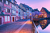 Canal waterfront view of traditional townhouses at dusk, Colmar, Grand Est, France