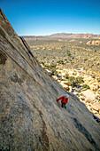 A young boy climbing a technical rock climb in Joshua Tree National Park, California.