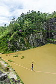 View from above of adventurous female slackliner balancing on rope, Dibs Quarry, Maripora, Sao Paulo State, Brazil
