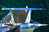 View from top of mast of trimaran with sailor climbing, Atlantic Ocean, Brittany, France