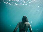 Rear view of woman swimming underwater, St. John, US Virgin Islands, USA