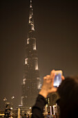 Woman capturing photos of Burj Khalifa in Dubai