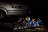 Couple sleeping near car at night, Batukaras, Java, Indonesia