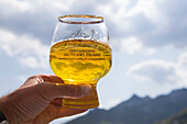 A Glass of craft beer (Biere du Mont Blanc) hold to the sky. This is at the end of the Tour du Mont Blanc, a classic trekking around the highest peak of the Alps, that goes through France, Italy and Switzerland.