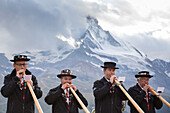 Four traditionally dressed locals of Zermatt play the Alphorn in front of the Matterhorn mountain.     With the passing of time, the alphorn almost totally disappeared as an instrument used by Swiss shepherds. It was only with the romanticism of the 19th