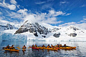Members of an expedition cruise to Antarctica sea kayaking in Paradise Bay beneath Mount Walker on the Antarctic peninsula. The Antarctic peninsula is one of the most rapidly warming areas on the planet.