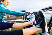 Two female runners in sportswear stretching hamstrings after jogging near Puget Sound, Seattle, Washington State, USA