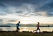 Side view of man and woman running along Puget Sound at sunset, Seattle, Washington State, USA