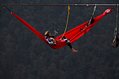 Side view of person lying in hammock and hanging on high line, Tijesno Canyon, Banja Luka, Bosnia and Herzegovina